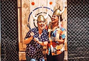 Two girlsposing with axes in front of a target board