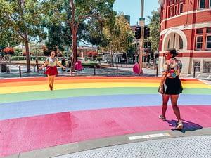 Two girls walking over rainbow painted walkway