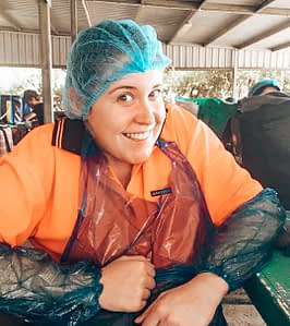 88 days of farm work - Girl smiling at camera with hair net and plastic apron and arm protectors on