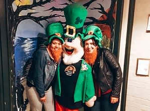 Two girls with green hats on posing with a leprechaun model
