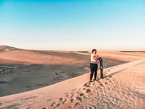 Lady standing at the top of a sand dune with a board in hand