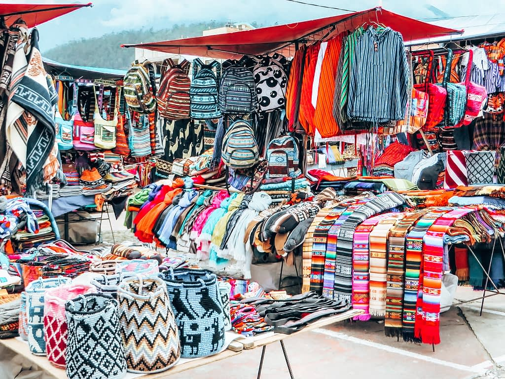 Otavalo Market - Stall selling colourful clothing and bags - Day Trips From Quito