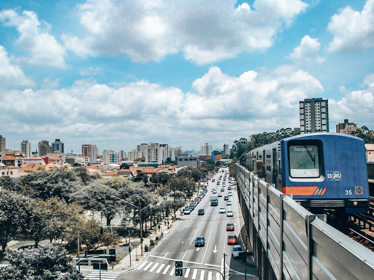 Rio Carnival Subway - Image of train entering platform above a busy highway road