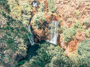 Litchfield National Park - Birdseye view of a waterfall surrounded by a red rock gorge and trees