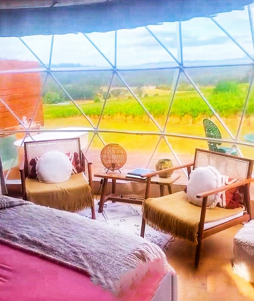 Domescapes Tasmania - Image of two chairs facing inwards with a dome window overlooking a vineyard - Tasmania Itinerary