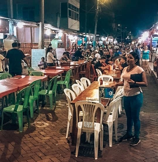 Busy street filled with dining tables