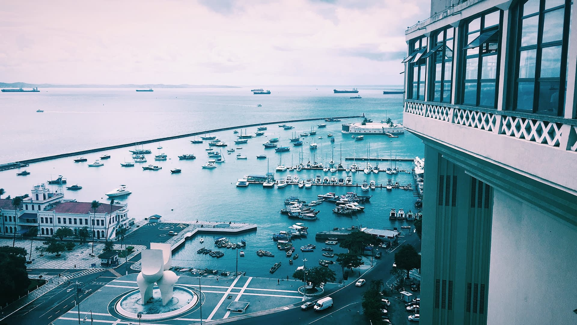 Elevator Salvador - Elevador Lacerda - Image of outdoor elevator overlooking beach port. filled with sail boats
