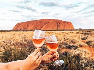 Uluru - Two wine glasses clinking with Uluru in the background