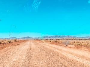 Image of dirt road under blue skies
