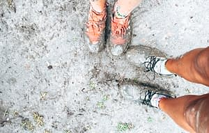 88 days of farm work - Picture of two people standing in wet mud with muddy trainers