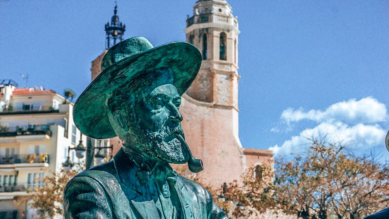 Amazing places near Barcelona - Sitges - A statue of man smoking a pipe with church steeple in the background