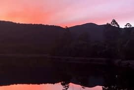 Lake Rosebery Foreshore Camp - Sunset over a lake with deep purple and pink hues in the sky - Lap of Tasmania