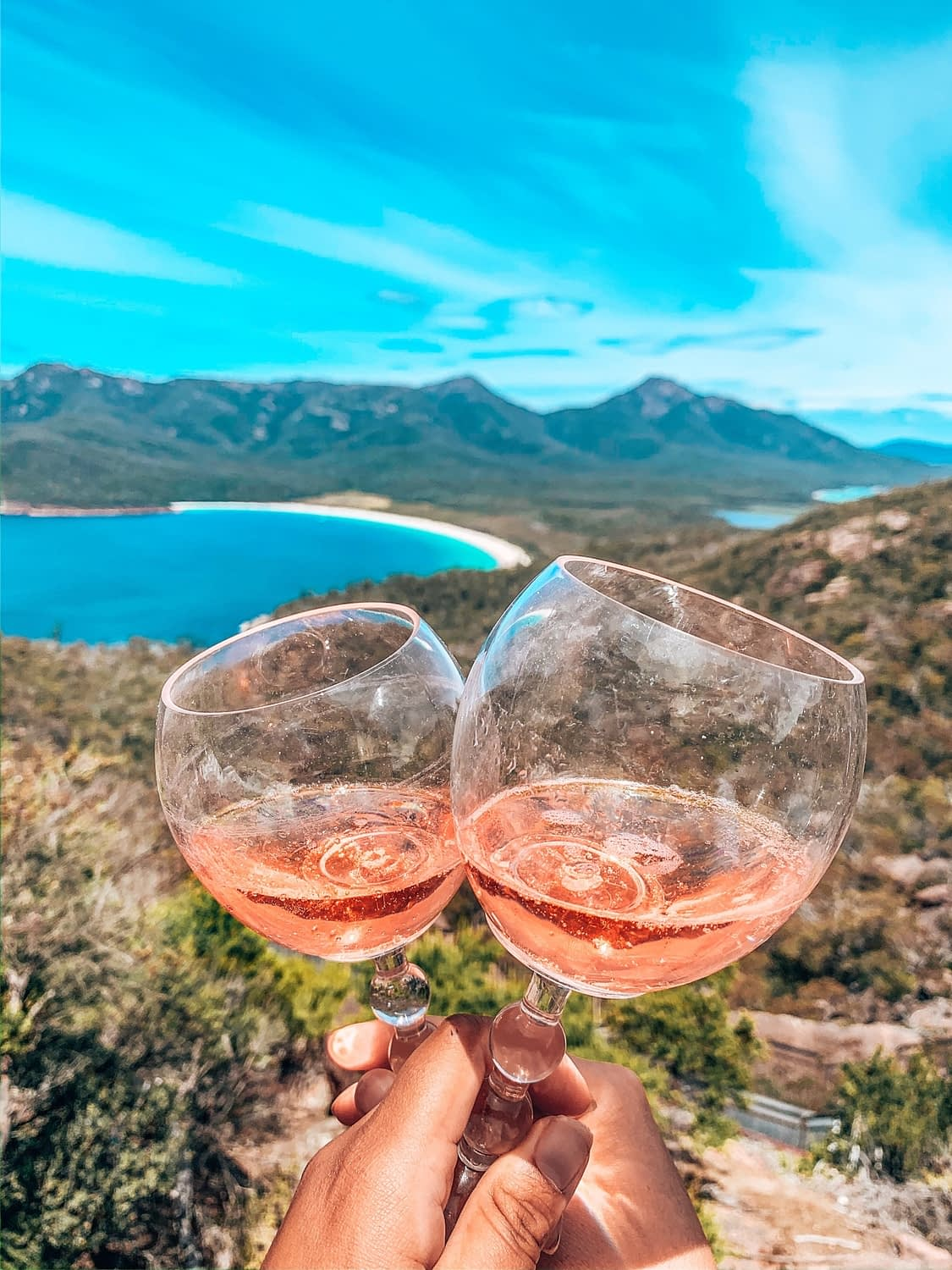 Freycinet WIne Glass Bay - Two wine glasses of Rosé clinking with wineglass bay visible through the glass - Lap of Tasmania