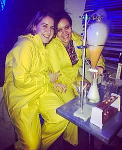 Two girls dressed in yellow jumpsuits drinking cocktails