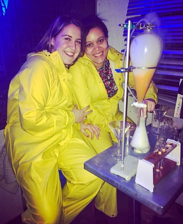 Unique Themed Cocktail Bars in London - Two girls dressed in yellow jumpsuits drinking cocktails