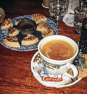 Cocktail served in a traditional tea cup and saucer with a plate of buttered crumpets
