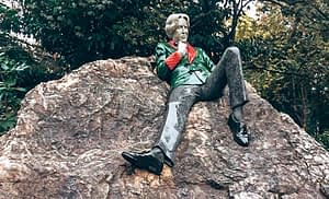 Statue of Oscar Wilde resting on a stone