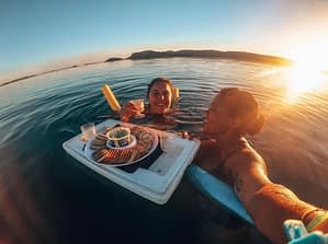 Two girls enjoying a tray of snacks whilst floating in a lake during sunset