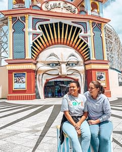 St Kilda Luna Park - Two girls posing outside large clown face entry with mouth as entry - Ultimate Guide To Melbourne