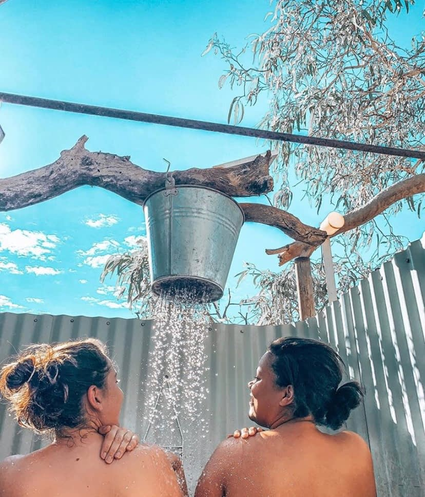 Two girls showering outside under a bucket shower