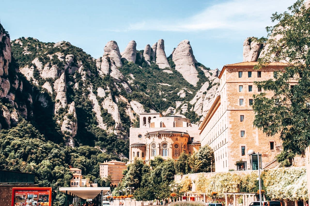 Amazing places to visit near Barcelona - Image of Montserrat - a Terracota building with mountains in the background