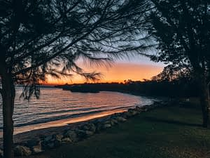 East Point Reserve, Darwin. Sunset overlooking a small beach, framed with palm trees