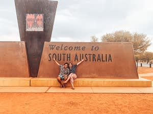 Two girls siting in front of large 'Welcome to South Australia' sign