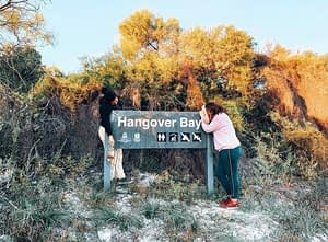 Two girls leaning over a sign which says Hangover Bay, holding a bottle of tequila. Famous stops from Perth to Darwin