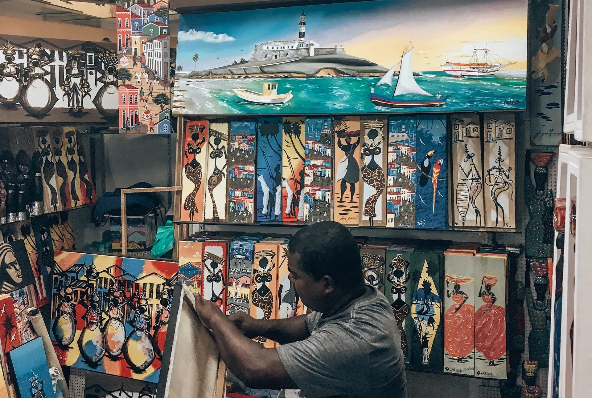 Mercado Modelo Salvador Brazil - Salvador Brazil Market - Indoor market stall selling colourful afro-brazilian art pieces. Things to Do in Salvador Brazil