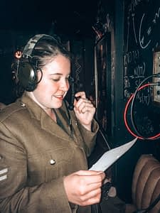 Girl speaking into an old telephone wearing military uniform