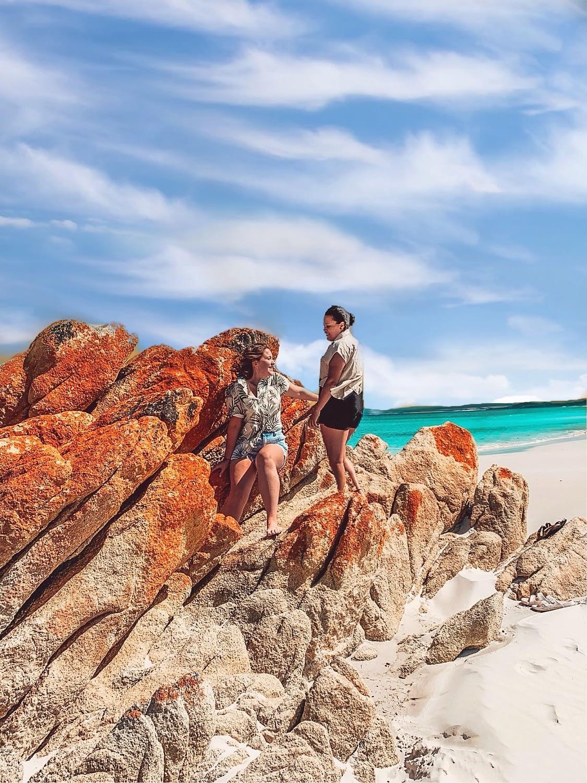 Bay of Fires Tasmania - Image of Two Girls Standing on burnt orange rocks overlooking the Ocean - Things To Do In Tasmania