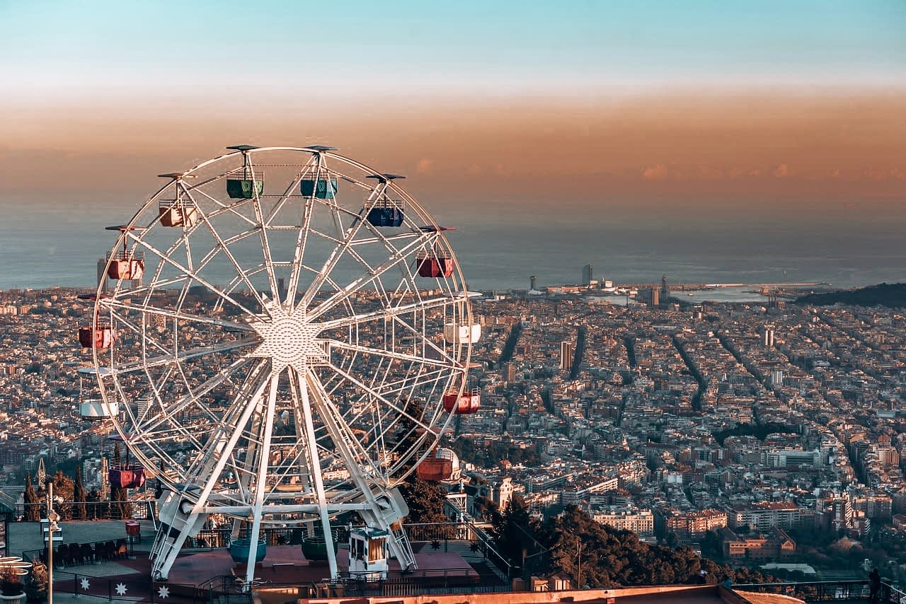 A Day In Barcelona - Tibidabo - Rainbow coloured ferris wheel on top of a cliff overlooking Barcelona city
