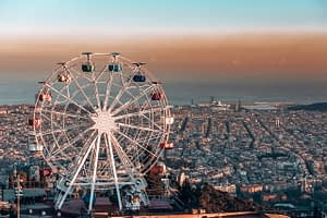 Rainbow coloured ferris wheel on top of a cliff overlooking Barcelona city