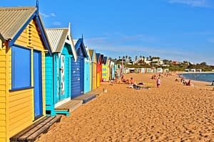 Brighton Beach Huts - Colourful beach huts next to yellow sand beach - Ultimate Guide To Melbourne
